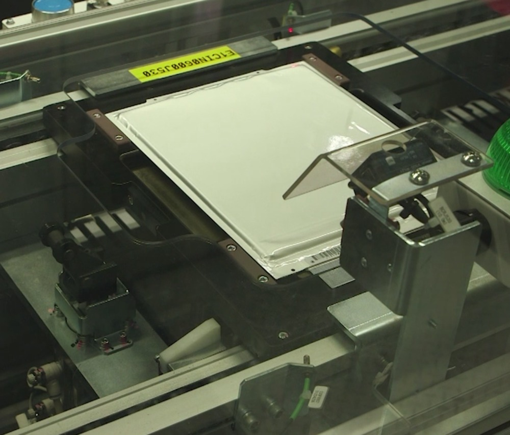 Battery cells are taken along a conveyor, with visual checks performed