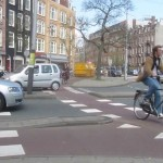 Bicyclists and cars easily sharing the road in Amsterdam's roundabouts